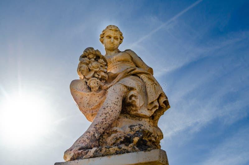 Estatua en la mujer de la puerta con las flores con el cielo azul en el fondo fotos de archivo