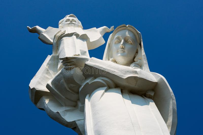 Estatua gigante de la Virgen María con Jesús en sus brazos contra un primer del cielo azul en Vung T fotografía de archivo