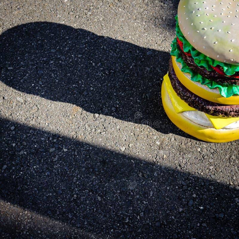Estatua grande de la hamburguesa en la trayectoria que camina del asfalto imagenes de archivo