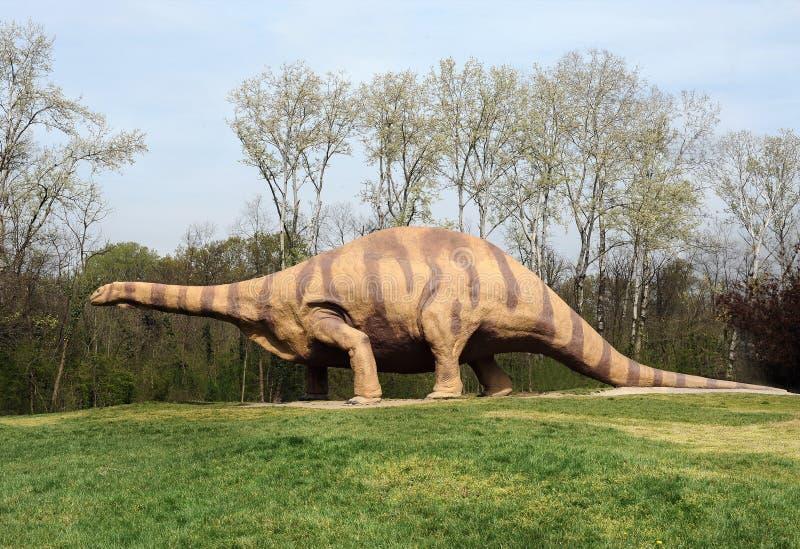 Estatua grande del Brontosaurus que se coloca en el parque herboso fotografía de archivo libre de regalías