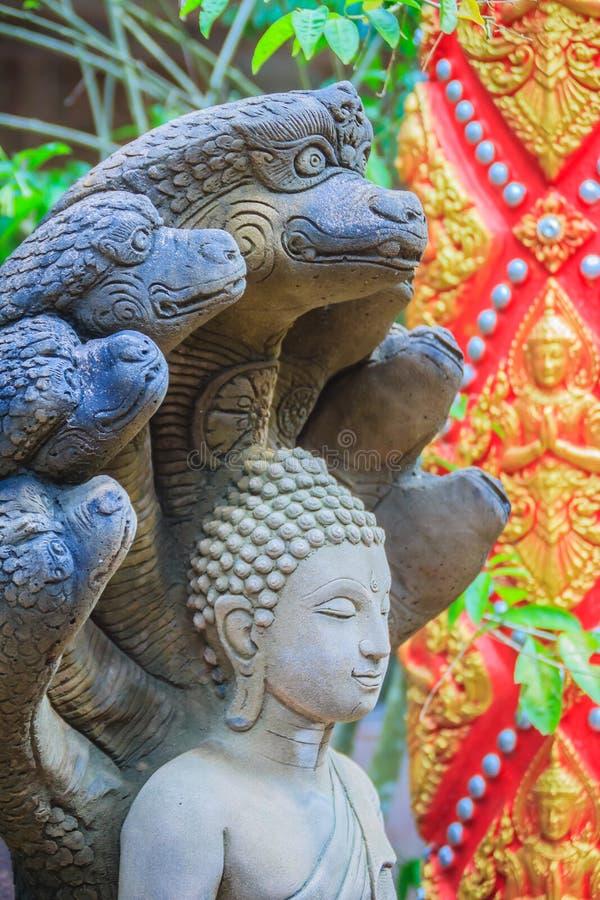 Estatua hermosa de Buda hecha de piedra y de la cubierta de la arena con las cabezas del Naga La estatua de piedra de Buda con si fotografía de archivo