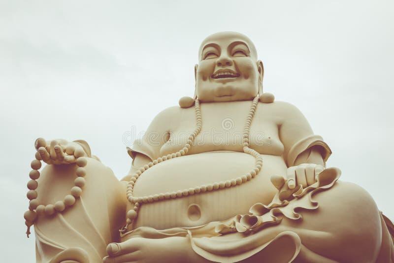 Estatua masiva del Buda sonriente que se sienta en el Vinh Tranh P foto de archivo libre de regalías