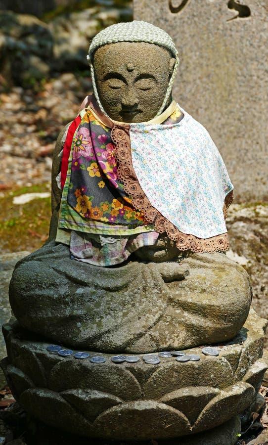 Estatua miniatura de Buda que se sienta dentro del cementerio de Okunoin foto de archivo
