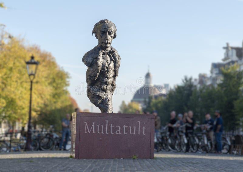 Estatua Multatuli en un puente del canal en Amsterdam, los Países Bajos imagenes de archivo