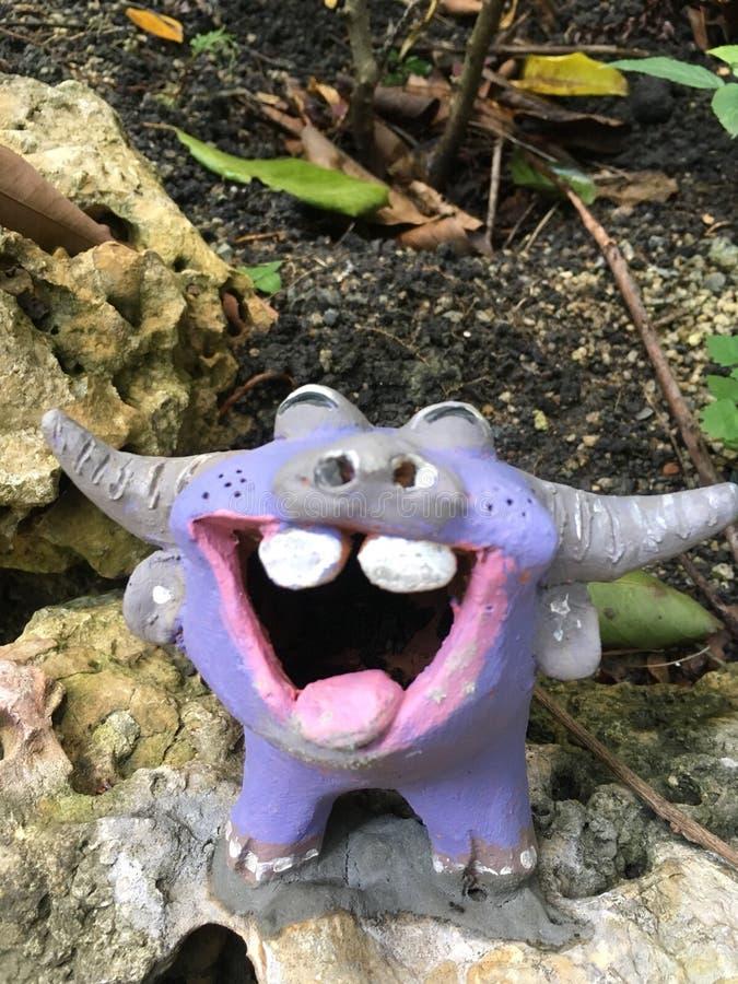 Estatua púrpura del búfalo de la sonrisa en el jardín fotos de archivo