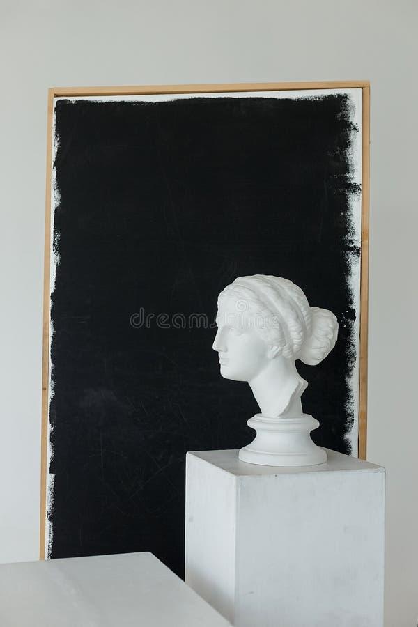 Estatua principal de la muchacha antigua del yeso en el cubo blanco grande en estudio con la bandera negra en un fondo con un cop imagen de archivo