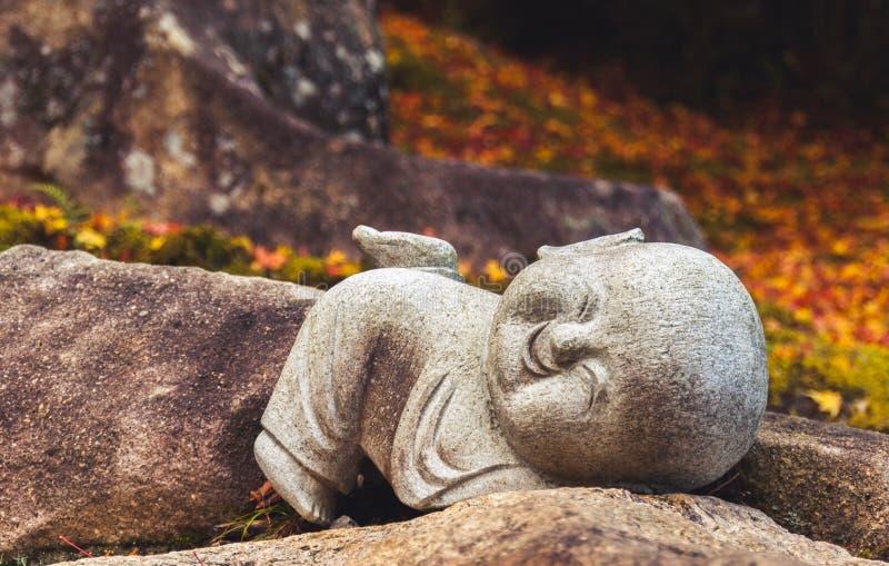 Estatua sonriente del jizo contra las hojas de otoño fotos de archivo libres de regalías