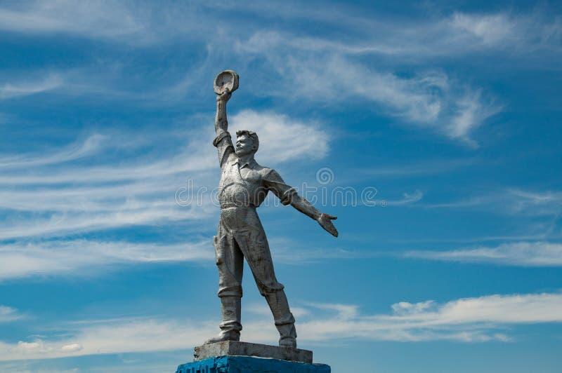 Estatua soviética del arte del trabajador en actitud potente con el fondo del cielo Monumento social del realismo en el campo de  imagenes de archivo