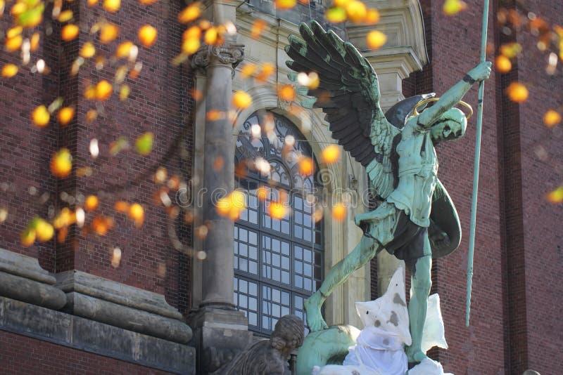 Estatua verde antigua antigua de Fontaine San Miguel del metal con bogae amarillo-naranja de la flor delante de la iglesia cristi fotos de archivo libres de regalías