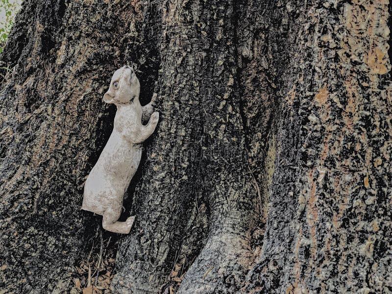 Estatua vieja de la ardilla y el árbol viejo imagen de archivo
