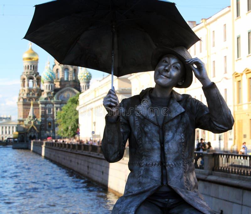 Estatua viva de un muchacho con el paraguas en un puente sobre el canal de Griboyedov foto de archivo