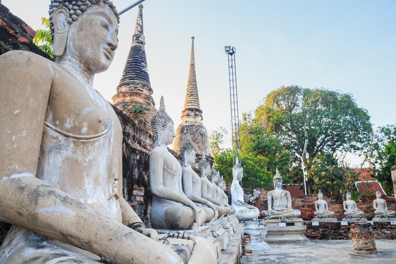 Estatuas alineadas de Buda que se sientan con la ruina antigua del templo en el wa imagen de archivo libre de regalías