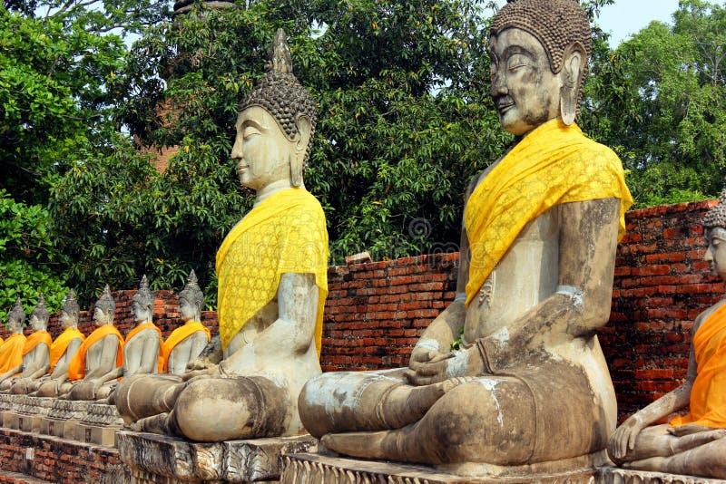 Estatuas antiguas de meditar a Buda que se sientan, en el templo viejo de Wat Yai Chaimongkol en Ayutthaya, Tailandia fotos de archivo