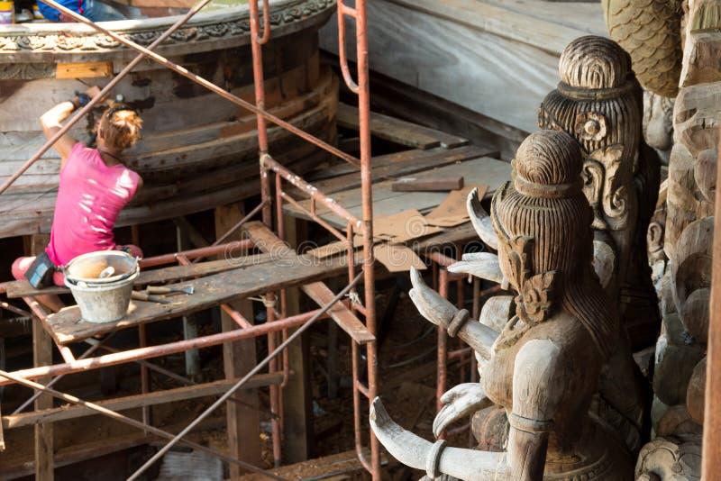 Estatuas budistas de madera con el reparador en fondo en el sitio de la restauración en el exterior del lado del santuario de la  fotografía de archivo libre de regalías
