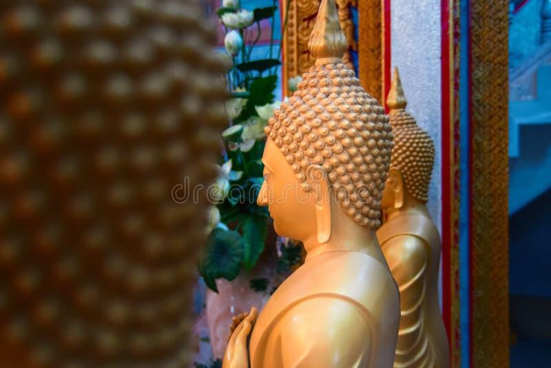 Estatuas de la cera de la vista lateral de monjes budistas en el templo Figuras de oro grandes Copie el espacio fotografía de archivo libre de regalías