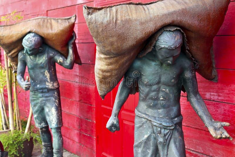 Estatuas de los hombres que llevan los sacos de arroz en el songkhla Tailandia fotos de archivo libres de regalías