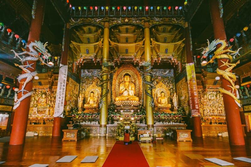 Estatuas de oro de Buda dentro del templo de Yakcheonsa Jeju, Corea del Sur fotografía de archivo libre de regalías