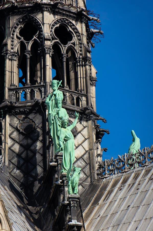 Estatuas de santos, la torre del chapitel en la fachada del sur de Notre Dame de Paris imágenes de archivo libres de regalías