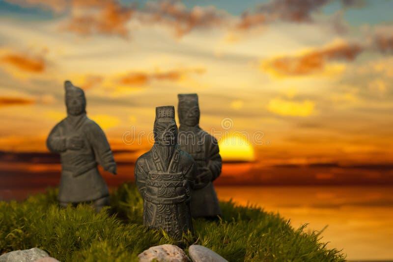 Estatuas en musgo en la puesta del sol imagen de archivo