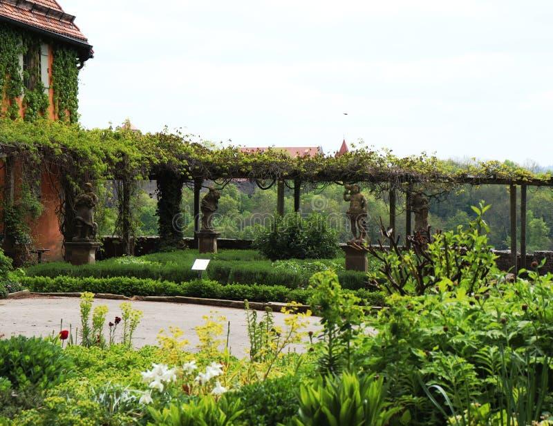 Estatuas y flores en el jardín al lado de la casa del jardín fotografía de archivo libre de regalías