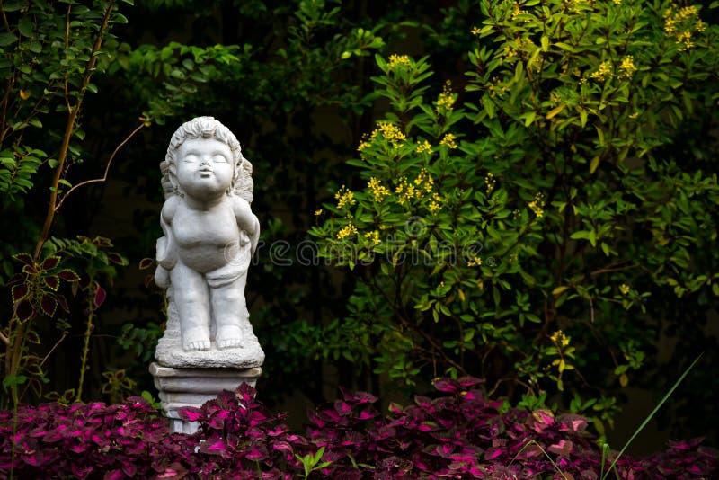 Estatueta branca de um suporte e de um beijo do anjo na casa do jardim no fotos de stock