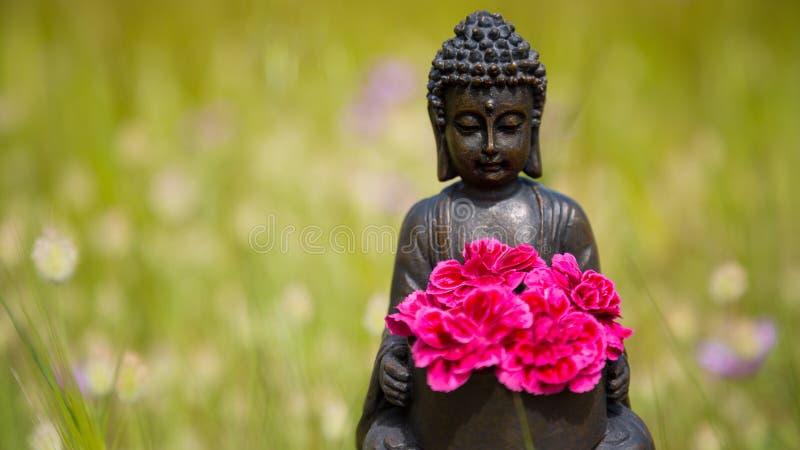 Estatueta da Buda com flores vermelhas fotografia de stock
