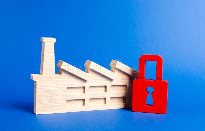 Estatueta da fábrica e cadeado vermelho A lei na proibição de facilidades industriais, o fechamento da produção prejudicial foto de stock royalty free