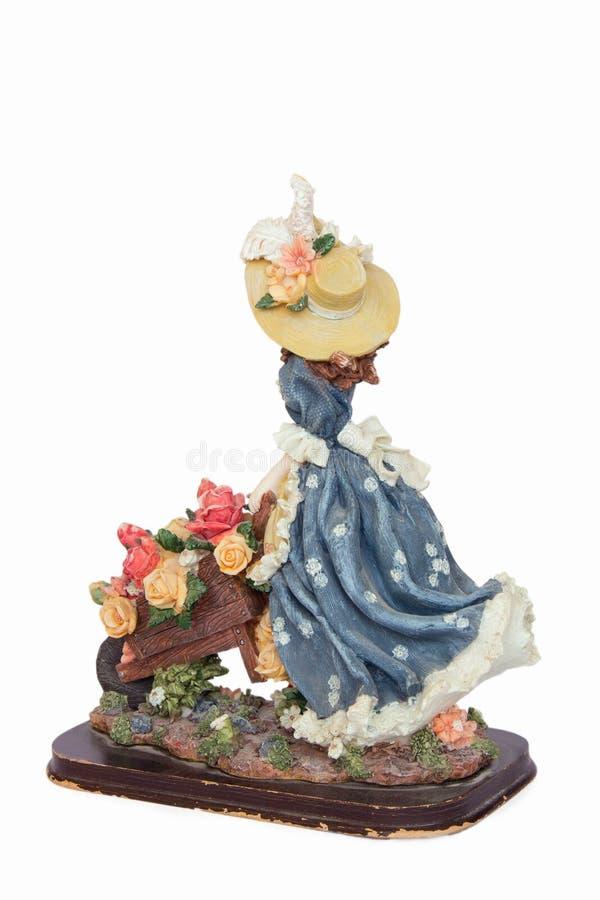 Estatueta da menina com o carrinho de mão completo das flores fotos de stock royalty free