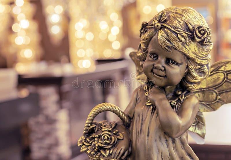 Estatueta de bronze de uma menina com uma cesta da flor no fundo do bokeh fotografia de stock royalty free