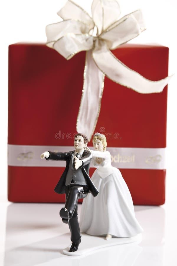 Estatueta de escape do noivo da noiva na frente do presente de casamento foto de stock
