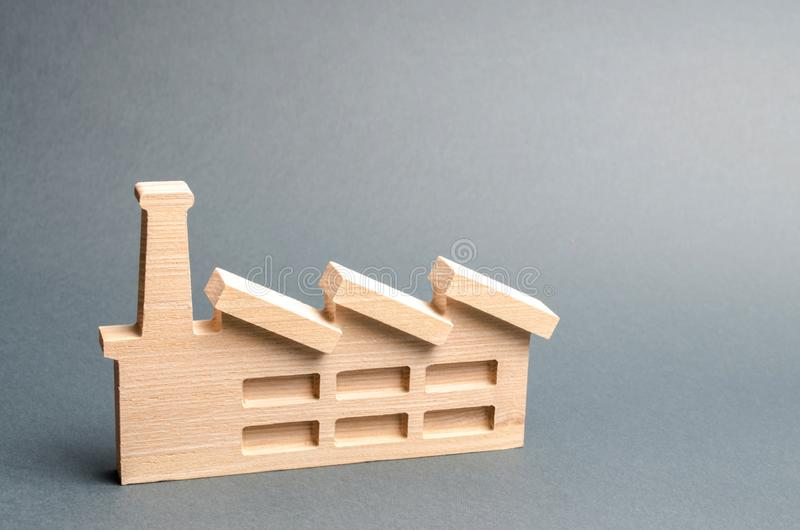 Estatueta de madeira de uma planta ou de uma fábrica em um fundo cinzento Reciclando mat?rias primas O conceito da ind?stria e da fotografia de stock