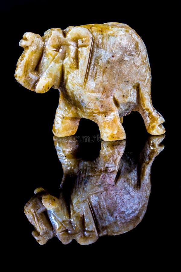Estatueta de pedra do elefante uma reflexão em um fundo de vidro preto imagem de stock