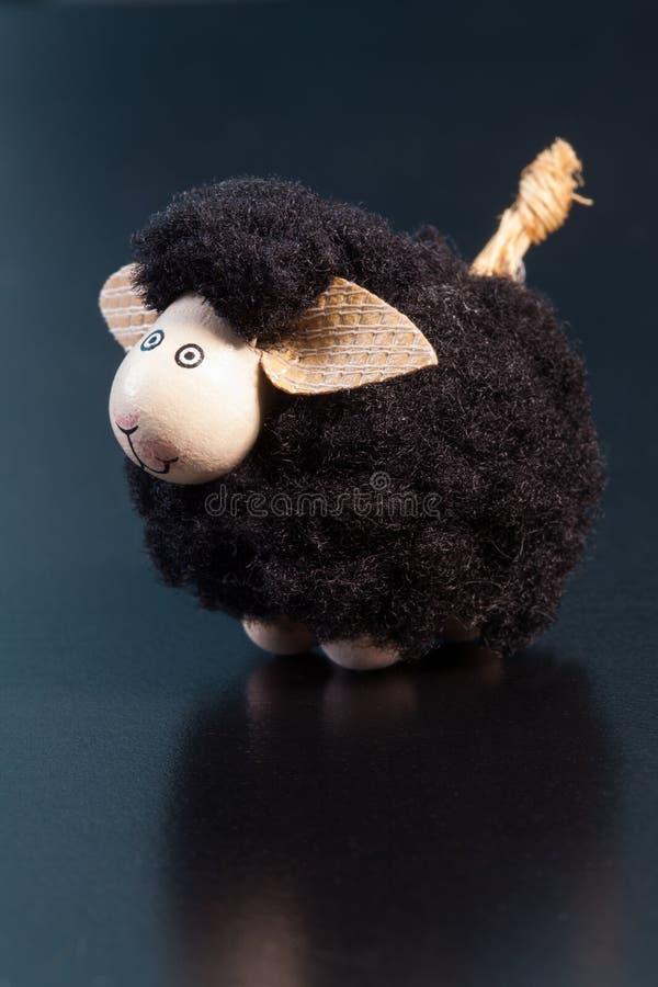 Estatueta de sorriso do brinquedo das ovelhas negras com orelhas grandes em uma superfície azul imagem de stock royalty free