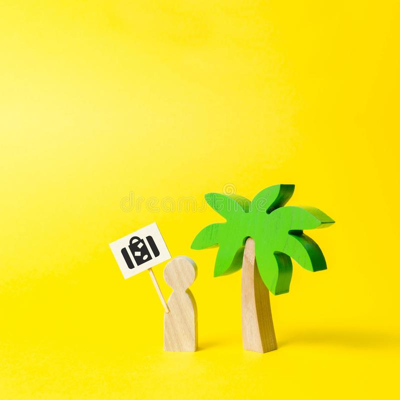 Estatueta de um homem com um cartaz com um saco sob uma palmeira em um fundo amarelo Agência de viagens Para encontrar experiênci imagens de stock