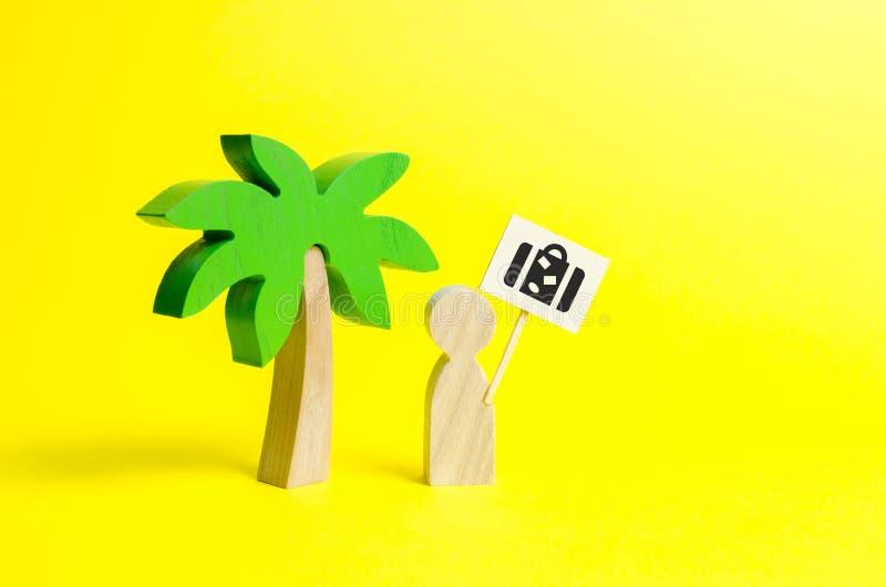 Estatueta de um homem com um cartaz com um saco sob uma palmeira em um fundo amarelo Conceito de querer uma viagem das férias fotografia de stock