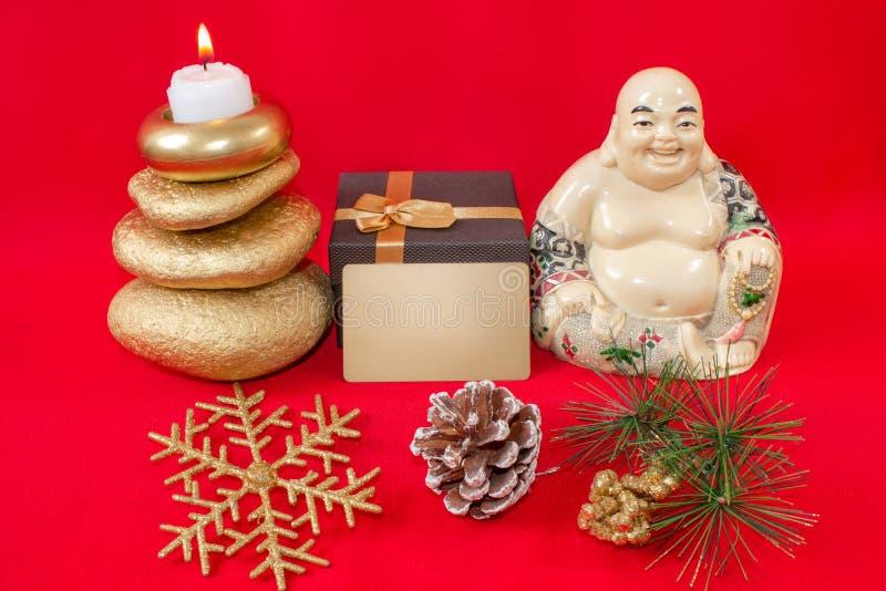 Estatueta de uma Buda de riso Hotei com pedras e uma vela, floco de neve e colisão, assim como uma caixa de presente e um cartão  fotos de stock