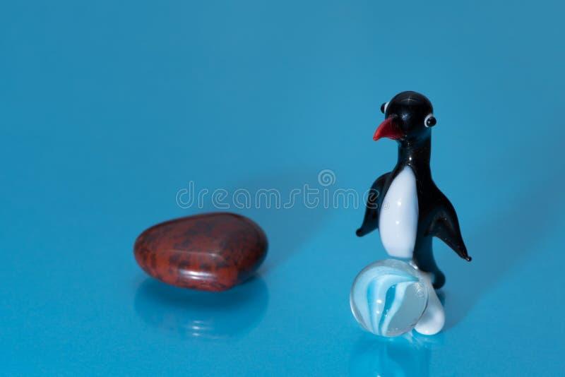 Estatueta de vidro de um pinguim pequeno bonito com um bico vermelho fotos de stock