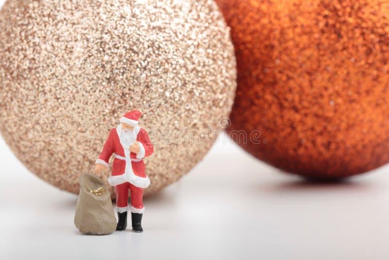 A estatueta diminuta de Santa Claus com seus presentes ensaca imagens de stock