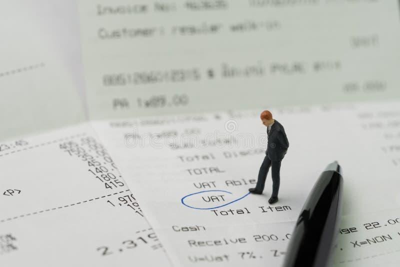 Estatueta diminuta do homem de negócio que está no invo impresso do pagamento foto de stock royalty free