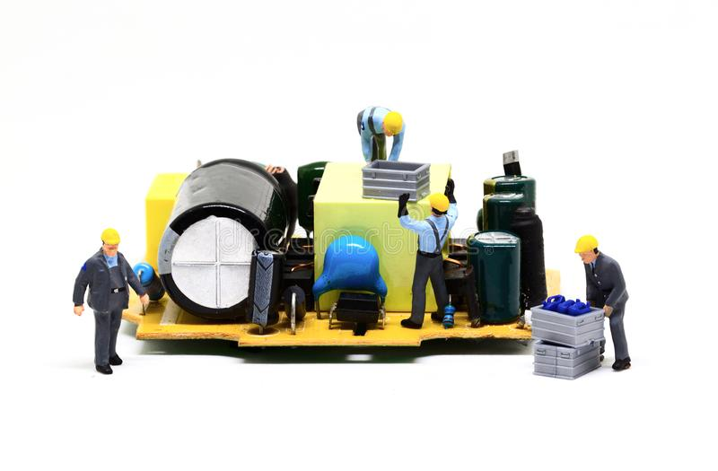 Estatueta diminuta do trabalhador e micro microplaqueta Homens na foto do macro do trabalho Molde da bandeira do reparo do comput fotografia de stock royalty free