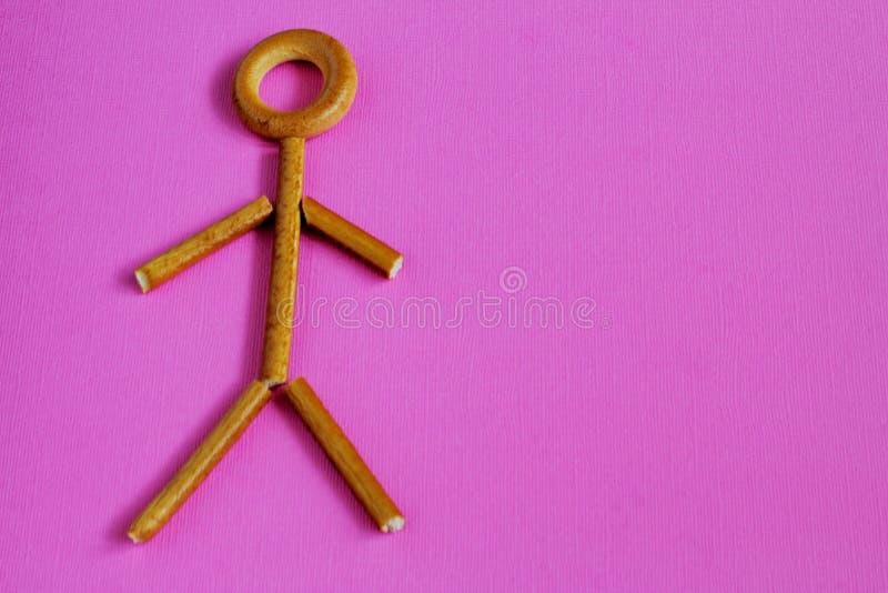Estatueta do homem pequeno feita de varas crocantes do bagel e do pão no fundo cor-de-rosa brilhante Atitude do †simbólico do c imagem de stock royalty free