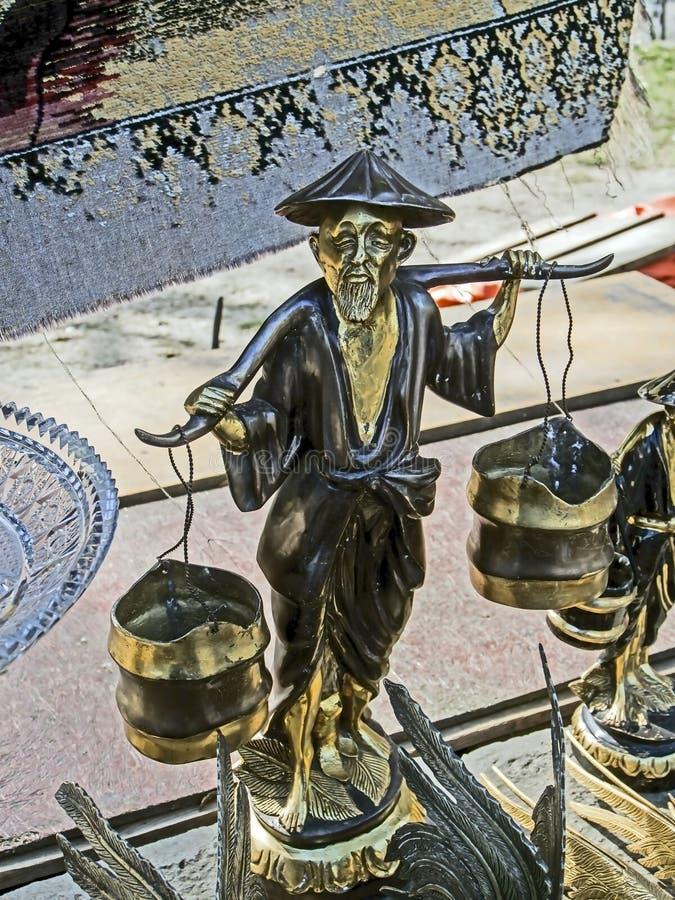 Estatueta do metal de um camponês chinês com um garfo em uma feira da ladra fotos de stock
