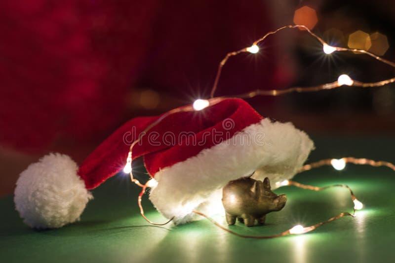 Estatueta dourada do porco com um chapéu de Santa, o conceito de ano novo imagem de stock