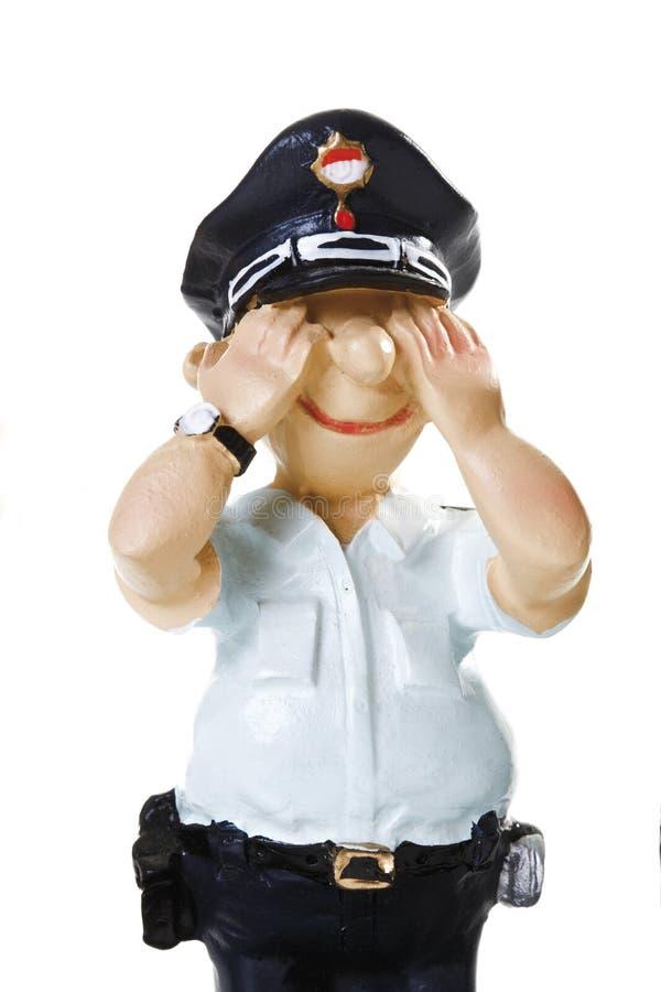 A estatueta plástica de um polícia, não vê nenhum mal, close-up fotografia de stock