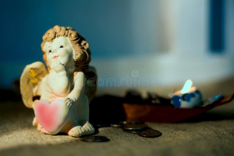 Estatueta pouco anjo com um coração que sonhe de velas ardentes fotografia de stock royalty free