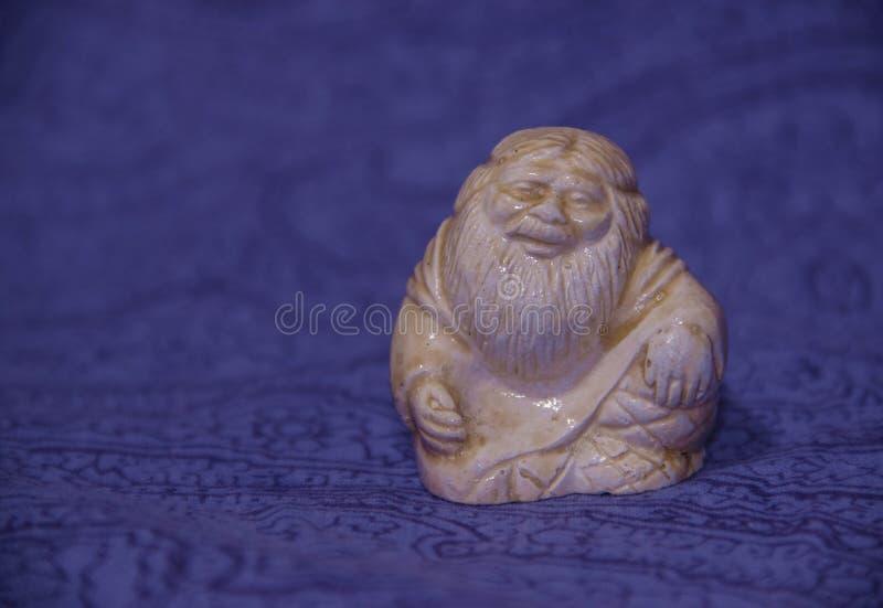 Estatueta prudente chinesa cerâmica que senta-se em um fundo azul fotografia de stock royalty free