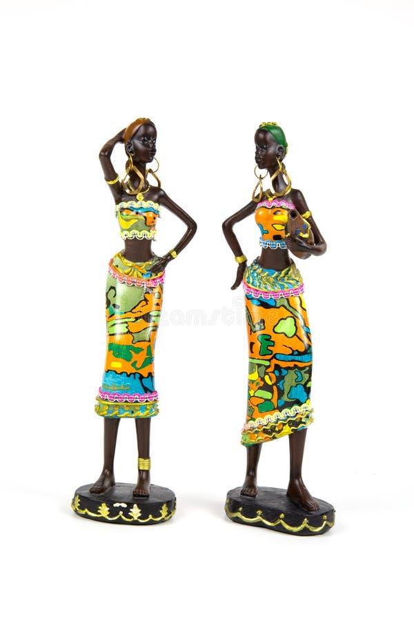 Estatuetas cer?micas Duas mulheres afro-americanos pintadas nos equipamentos nacionais brilhantes isolados no fundo branco imagens de stock royalty free