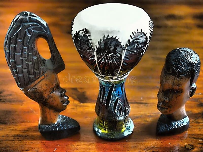 Estatuetas de madeira da cabeça e de uma mulher de um homem e entre elas um cilindro para rufar ilustração royalty free