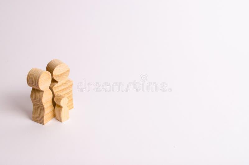 Estatuetas de madeira dos pais e de uma criança em um fundo branco Minimalismo o conceito da família e a educação das crianças imagens de stock royalty free