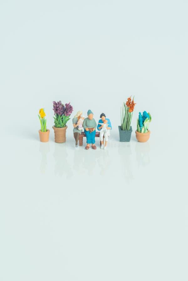 Estatuetas diminutas - 3 gerações de povos no fundo branco foto de stock
